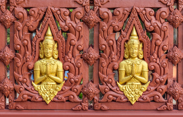 Row of Buddha statues on Buddhist temple wall