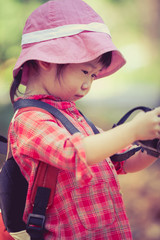 Asian girl checking photos in digital camera. Vintage picture style
