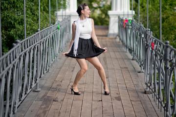 Dancing girl in short skirt in city park
