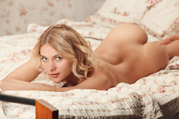 Sensual blonde woman posing naked or nude in bed