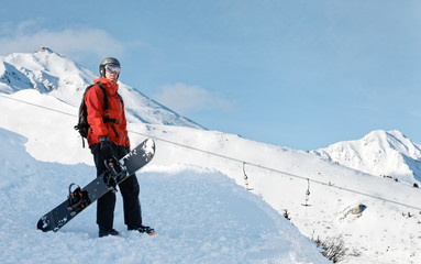 Snowboarder holding a snowboard against  panoramic mountain background with a copy space