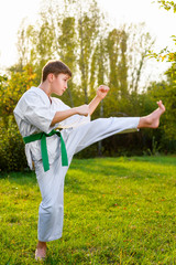 boy in white kimono during training karate exercises at summer outdoors