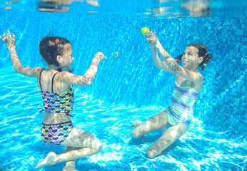 Children swim in pool or sea underwater, happy active girls have fun under water