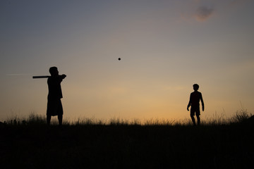 Silhouette of father and son playing baseball outdoors