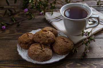tea and cookies and fresh flowers  on a wooden table