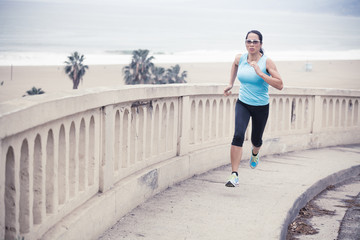 Woman running up a sidewalk by the beach, Santa Monica, California, America, USA