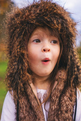 Portrait of young girl in fluffy hat making a funny face