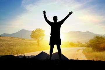 Силуэт туриста мужчины человека на фоне солнца, гор, дороги (двойная экспозиция)