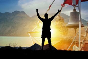 Силуэт туриста мужчины человека на фоне солнца, гор, колокола (двойная экспозиция)