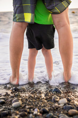 Ноги ребенка и его отца стоят в морской пене на камнях, любуясь закатом.