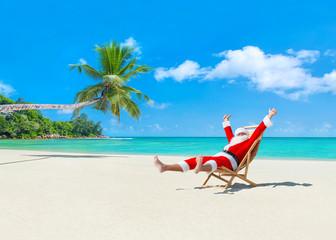 Christmas Santa Claus on deckchair enjoing palm sady ocean beach