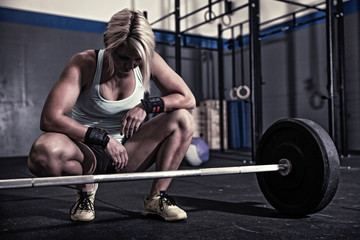 Woman in gym about to lift weights
