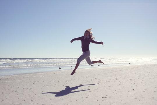 Mature woman running along the beach, Jacksonville, Florida, America, USA
