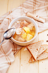 healthy hot lunch , chicken soup with potatoes , carrots , chicken breast , spices and rye bread on a wooden background