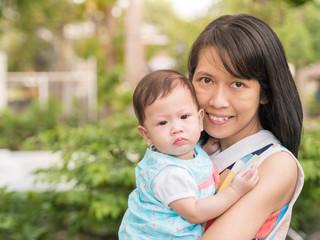 Beauty Asian mother carry cute baby in garden outdoor.