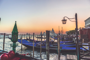 Beautiful romantic view of gondola secured to a wooden pier during sunset in Grand Canal in Venice, Italy