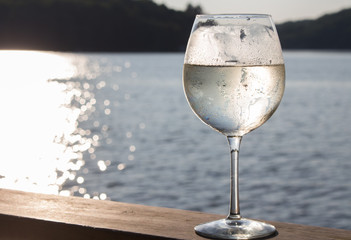 White wine spritzer on the wooden deck of a Canadian cottage summer sunset landscape