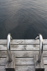 Closeup of a steel ladder on a wooden dock leading into a northern lake still life