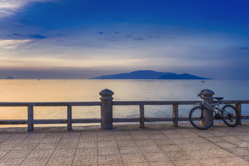 Old, rusty bicycle stands on the quay before dawn