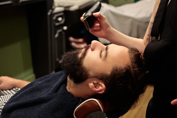 Young man cutting his beard