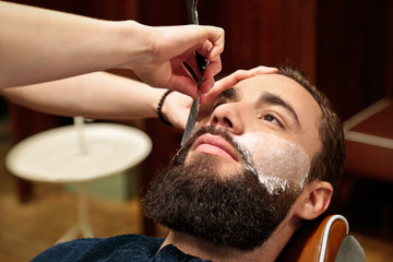 Hairdresser shaving  a beard