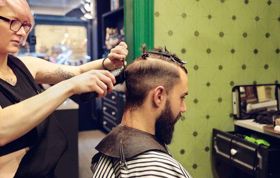 Female hairdresser cutting hair to a man