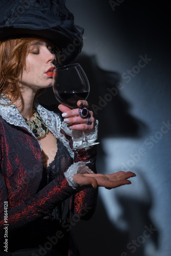 Wall mural Fashionably dressed woman with a glass of alcohol