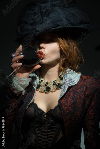 Wall mural Fashionably dressed woman with a glass of red wine