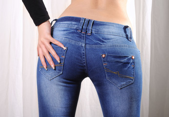 Sexy butt of a woman wearing tight skinny jeans, a hand on her butt.