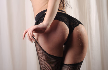 Beautiful buttocks of a woman wearing fishnet stockings, lace panties and suspenders.