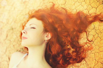 Beautiful young woman portrait with long curly red hair.