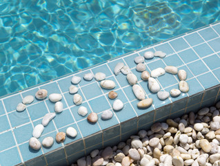 "The inscription "" 2016 "" is laid out by pebble on a pool side"