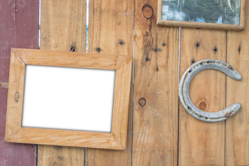 old vintage wooden photo frame and old rusty horseshoe on vintag