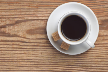 White saucer and cup of coffee with two cane sugar pieces on rustic wooden table background top view have place for text