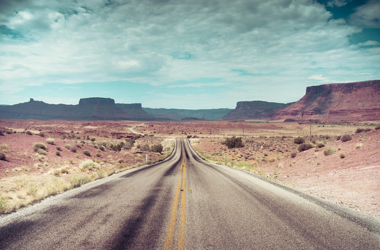 Open Road and possibilities. Road in Arches National Park. Artistic Instagram style processing.
