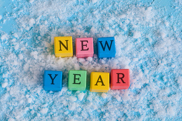 Happy New Year text written on the toy wooden color cubes. On snow background