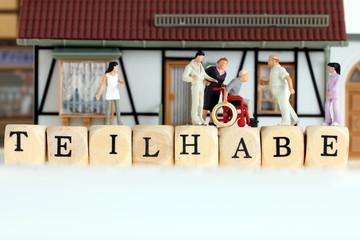"""Rollstuhlfahrer auf Buchstaben """"Teilhabe"""" Männchen, Hilfe, Solidarität"""