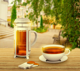 Black tea bags with cup and french press on background