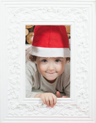 girl in Santa Claus's cap looks out through  frame for  picture