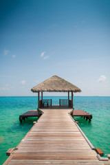 Papiers peints Bestsellers Wooden pier leading to cyan Indian Ocean and blue sky
