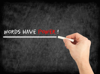 Words have power - hand writing text on chalkboard.