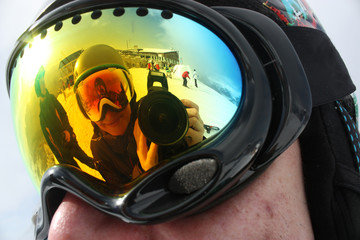 Young snowboard woman reflection in snowboard mask.