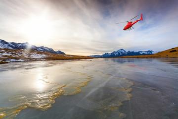 Elicottero rosso in volo su lago ghiacciato