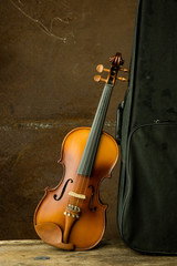 vintage violin resting against an old steel background