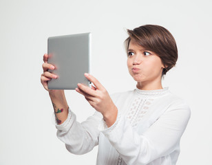 Amusing woman making funny face and taking selfie with tablet