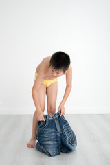 Asian shy boy with underwear on gray background.