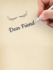 "Hand writing ""Dear Friend"" on aged sheet of paper."