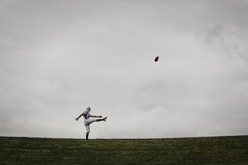 A football player in uniform, practicing his kicking. Ball in mid air.