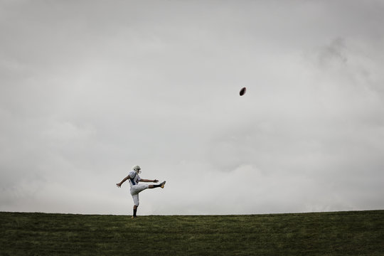 American football player kicking ball i field