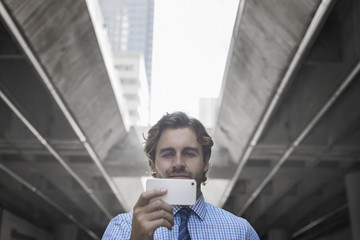 A man on a city street, holding a mobile phone taking a selfie, with an urban walkway and tall buildings in the background.